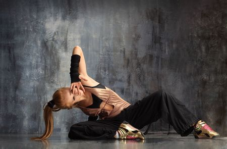 dance pose: modern style dancer posing behind studio background Stock Photo