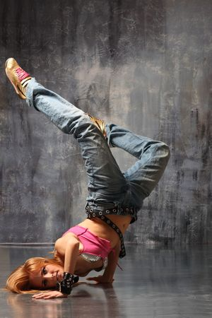 headstand: modern style dancer posing on studio background