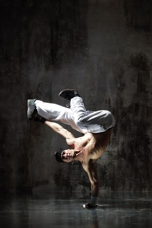 breakdancer: modern style dancer posing on dirty grunge background