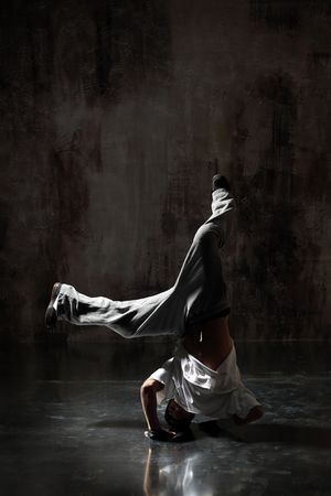 headstand: modern style dancer posing on dirty grunge background