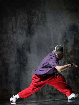 breakdance:  modern dancer poses in front of the old dirty wall