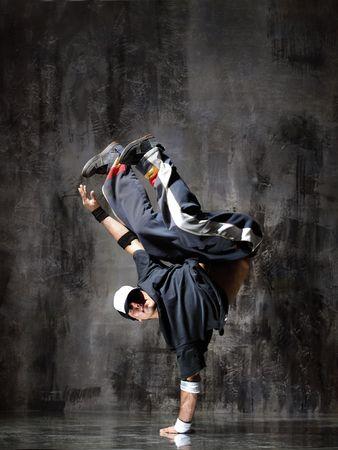 acrobacia: moderna bailarina plantea frente a la pared del viejo y sucio