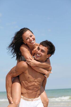pareja saludable: bonita pareja posando en la costa del mar de arena