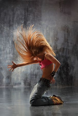 moderne danser vormt voor de oude vuile muur Stockfoto