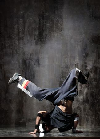 breakdancer: modern dancer poses in front of the old dirty wall