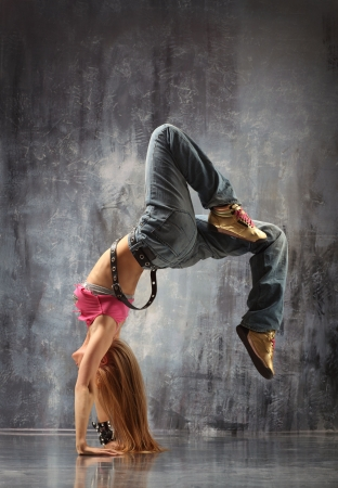 breakdancer: modern dancer poses in front of the gray wall