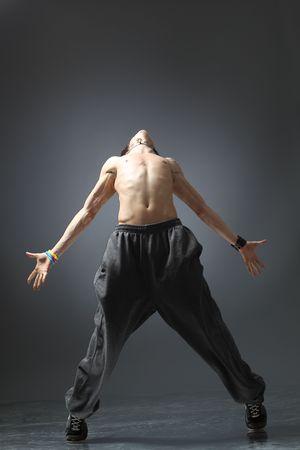 растягивание: создает современные танцовщица перед сером фоне