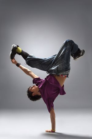 breakdancer: modern dancer poses in front of the gray background