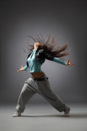 modern dancer poses in front of the gray background