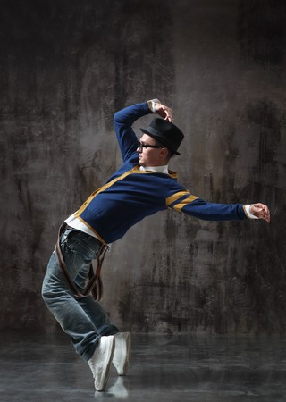 breakdancer: modern style dancer posing on studio background