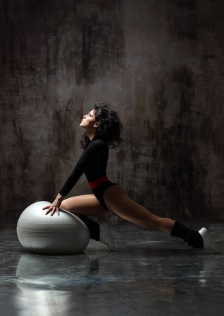 balance ball: sexy female doing aerobic exercises in sports clothing