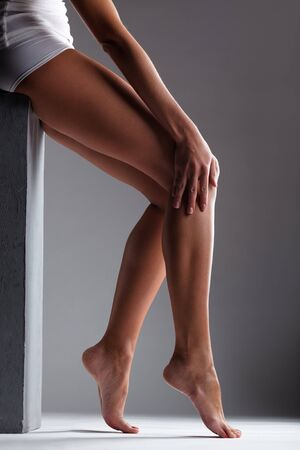 Smooth female legs on a grey background photo
