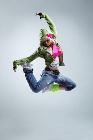 ragazze che ballano: ballerino di stile moderno saltando su sfondo studio Archivio Fotografico