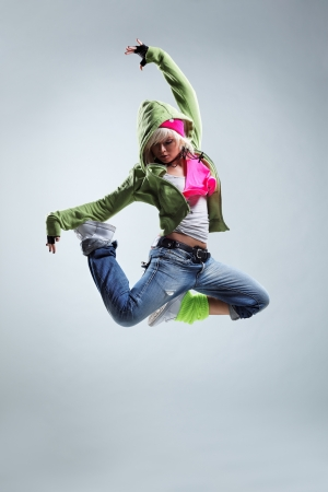 dancing pose: modern style dancer jumping on studio background Stock Photo