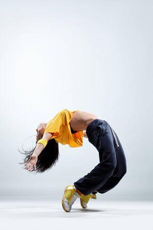 acrobacia: bailar�n de estilo moderno posando sobre fondo de estudio Foto de archivo