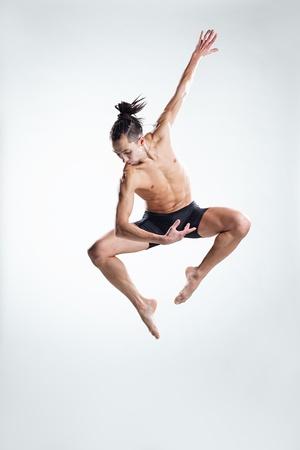 male ballet dancer: modern style dancer posing on studio background