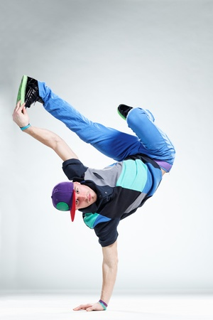 breakdance: modern style dancer posing on studio background