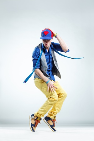 cool boy: modern style dancer posing on studio background