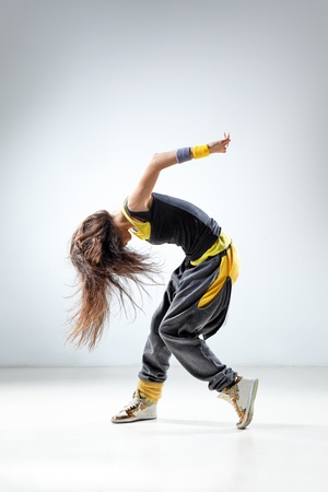 hip hop dancer: young and beautiful dancer posing on studio background