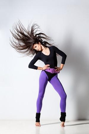 danza moderna: joven y hermosa bailarina posando en el estudio de antecedentes