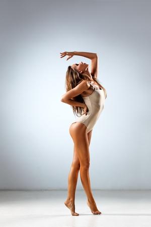 leotard: young and beautiful dancer posing in studio