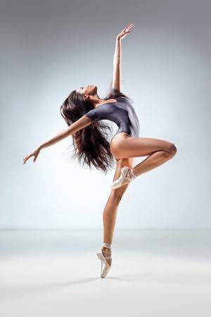 acrobatics: young and beautiful dancer posing in studio