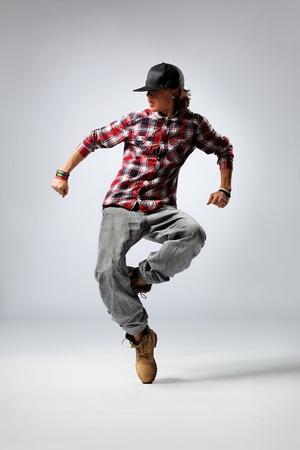 hip-hop dancer posing on studio background