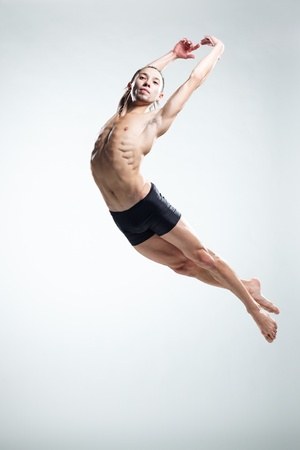 acrobatic: modern style dancer posing on studio background