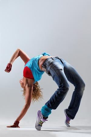 junge und schöne Tänzerin posiert auf Studio-Hintergrund