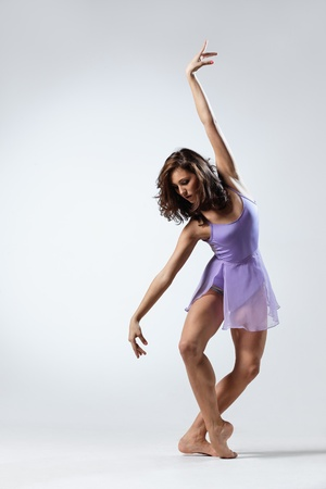 young and beautiful dancer posing on studio background photo