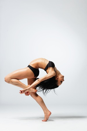 dancing pose: young and beautiful dancer posing on studio background