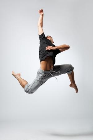 akrobatik: junge und sch�ne T�nzerin posiert auf grauem Hintergrund Studio