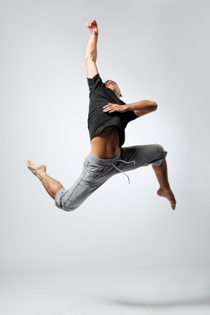 acrobatics: young and beautiful dancer posing on studio grey background