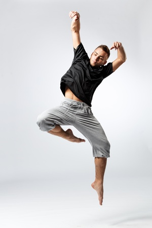 young and beautiful dancer posing on studio grey background