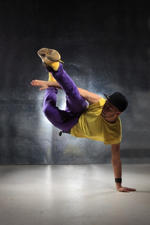 breakdance: young and beautiful dancer posing on studio background