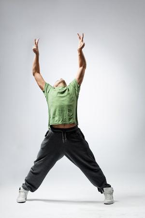 ballet hombres: joven y hermosa bailarina posando en el estudio de fondo gris