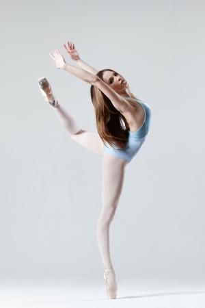 スタジオの背景にポーズをとって若い美しいダンサー