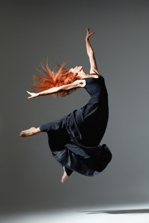 young beautiful dancer posing on a studio background photo