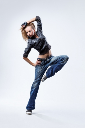 dancing pose: young beautiful dancer posing on a studio background