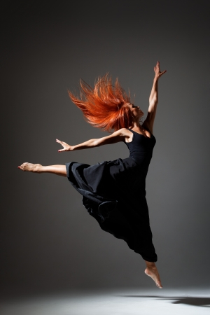 young beautiful dancer with red hair jumping on a dark studio background photo