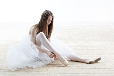 ballet shoes: young beautiful dancer posing on a studio background