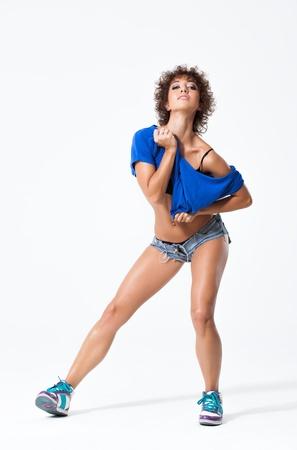 junge schöne Tänzerin posiert auf einem Studio-Hintergrund