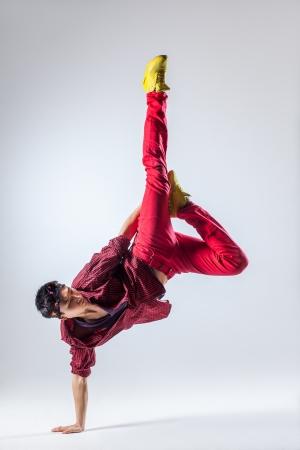 acrobacia: joven y bella bailarina posando sobre un fondo de estudio