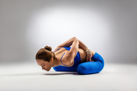 young beautiful yoga posing on a gray studio background photo