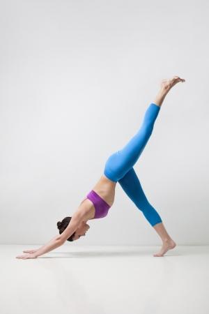 young beautiful yoga posing eka pada adho mukha svanasana on a gray studio background