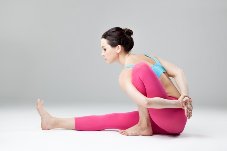 young beautiful yoga posing  on a studio background