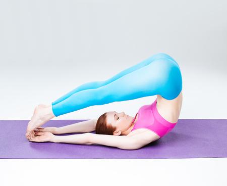 young beautiful yoga posing  on a studio background photo