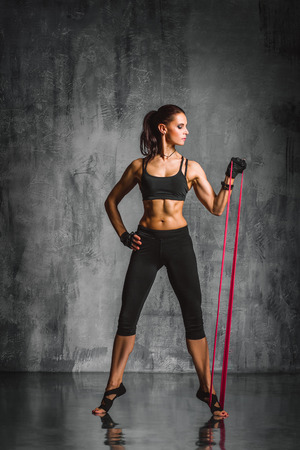 young beautiful sporty woman posing on studio background photo