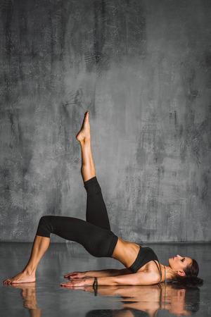 in action: joven y bella mujer deportivo posando en el estudio de fondo Foto de archivo