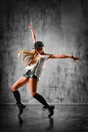 danza moderna: joven y bella bailarina posando en el estudio de fondo